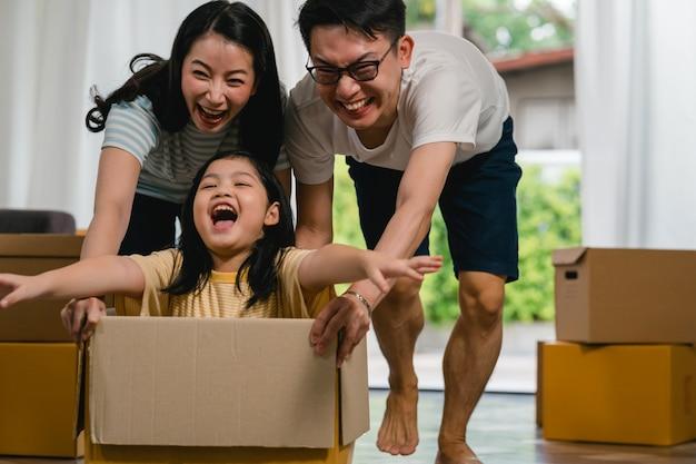Glückliche asiatische junge familie, die den spaß lacht hat, in neues haus umzuziehen. japanische eltern bemuttern und der vater, der aufgeregtem reiten des kleinen mädchens helfend lächelt, das in der pappschachtel sitzt. neues eigentum und umzug.