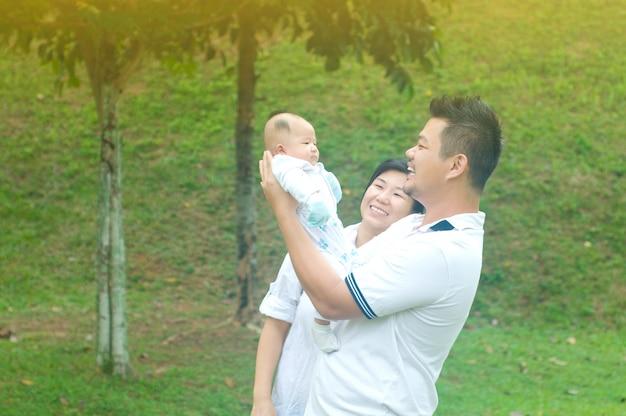 Glückliche asiatische junge familie, welche die zeit im freien an einem sommertag verbringt