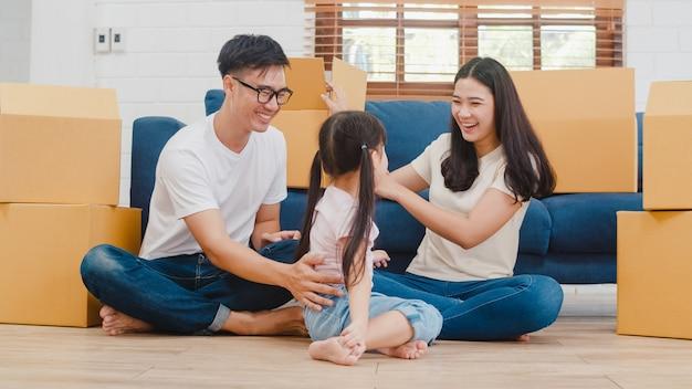Glückliche asiatische junge familienhausbesitzer im neuen haus