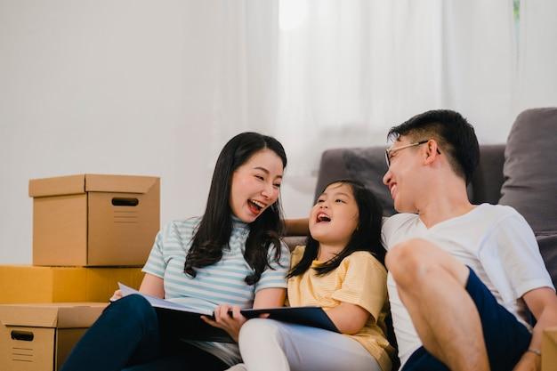 Glückliche asiatische junge familienhausbesitzer kauften neues haus. chinesische mutter, vati und tochter, die das vorwärtsschauen zur zukunft im neuen haus umfassen, nachdem sie in den umzug umgezogen sind, der zusammen auf boden mit kästen sitzt.