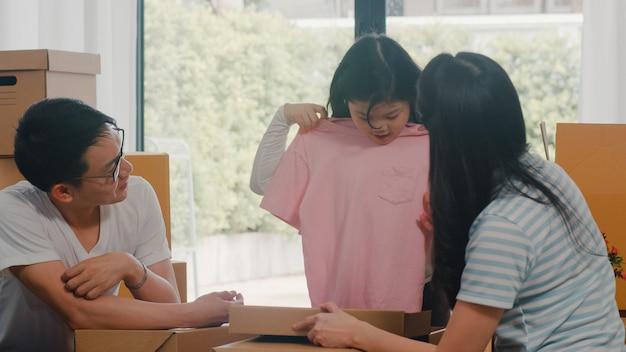 Glückliche asiatische junge familienverlagerungsumzüge vereinbaren im neuen haus. aufgeregte koreanische eltern packen pappschachteln zusammen mit der kleinen tochter aus, die kleidung im wohnzimmer am haus an beweglichem tag hält.