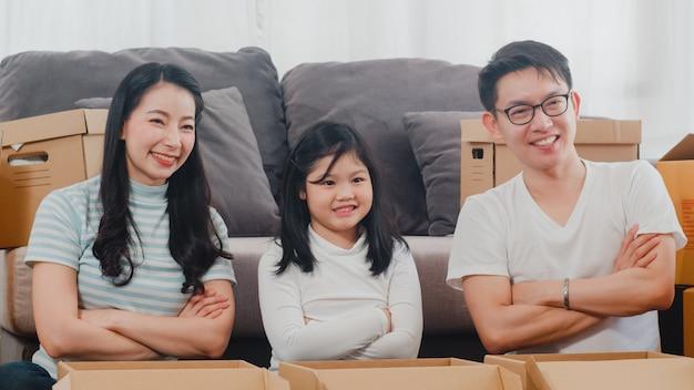 Glückliche asiatische junge familienverlagerungsumzüge vereinbaren im neuen haus. chinesische eltern und kinder öffnen die pappschachtel oder paket, die im wohnzimmer an beweglichem tag auspacken. immobilien, darlehen und hypothek.