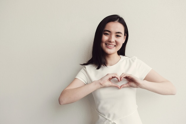 Glückliche asiatische junge frau, die ihre hände in der herzform macht