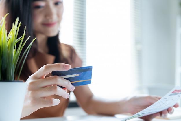 Glückliche asiatische junge frau, die mit leichtem leben für lohn ihre monatsausgabenrechnungen durch kreditkarte lächelt
