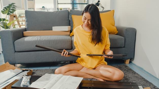 Glückliche asiatische junge frau, die schachtel auspackt und die anweisungen liest, um neue möbel zusammenzubauen
