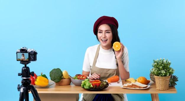 Glückliche asiatische junge frau im modeblickstil und schießendes video mit kamera, die essen kocht
