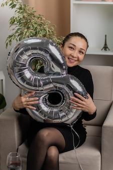 Glückliche asiatische junge frau im schwarzen kleid, das auf einem stuhl mit ballon der form acht sitzt, der fröhlich im hellen wohnzimmer lächelt, das internationalen frauentag feiert