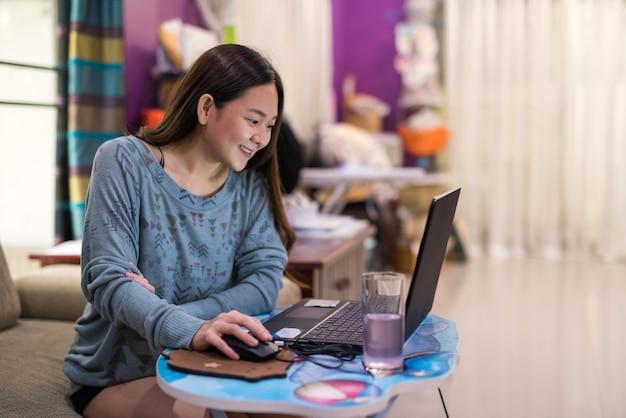 Glückliche asiatische junge geschäftsfrau arbeiten von zu hause im wohnzimmer, um covid-19-pandemie zu verhindern. bleiben sie sicher im haus, quarantäne, soziales distanzierungskonzept.