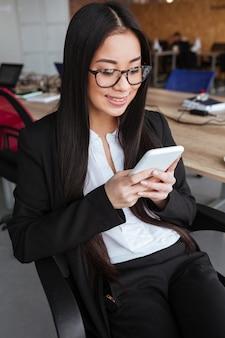 Glückliche asiatische junge geschäftsfrau, die sitzt und smartphone im büro benutzt