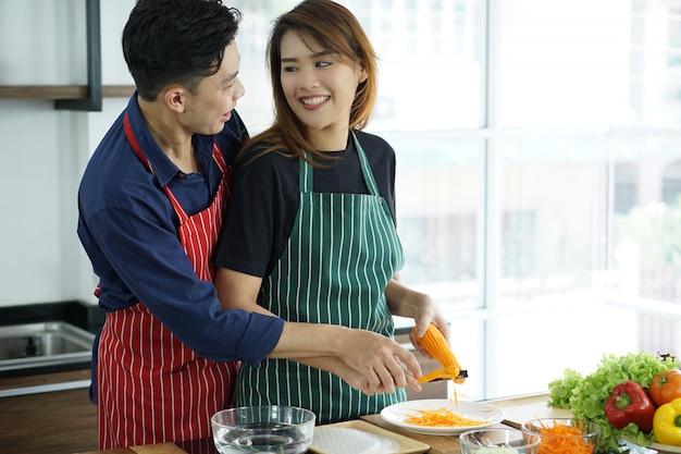 Glückliche asiatische junge paare, die lebensmittel in der küche kochen