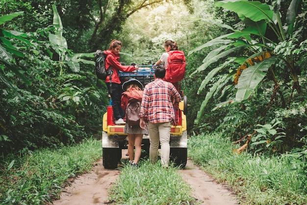 Glückliche asiatische junge reisende mit 4wd fahren auto weg von der straße im wald, junges paar, das mit rucksäcken geht und zwei andere genießen auf 4wd antriebsauto. junge gemischte rasse asiatische frau und mann.