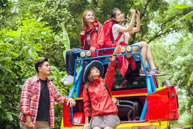 Glückliche asiatische junge reisende mit 4wd fahren auto weg von der straße im wald, junges paar, das nach richtungen auf der karte sucht und zwei andere genießen auf 4wd antriebsauto. junge gemischte rasse asiatische frau und mann.