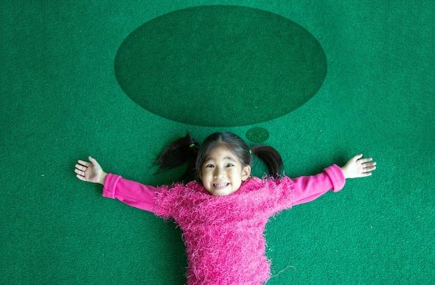 Glückliche asiatische kinder öffnen hand auf grünem gras und kreisform wie idee nach innen