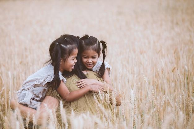 Glückliche asiatische kindermädchen, die ihre mutter umarmen und spaß haben, mit mutter auf dem gerstengebiet zu spielen