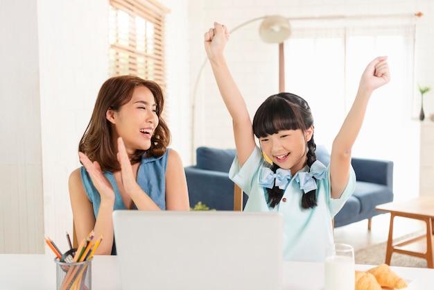 Glückliche asiatische kleine junge studentin der homeschool, die lernt, auf tisch zu sitzen, der mit seiner mutter zu hause arbeitet.