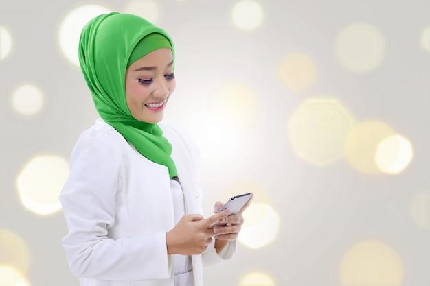 Glückliche asiatische moslemische frau, die ein telefon hält