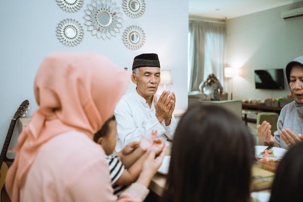 Glückliche asiatische muslimische familie, die betet, bevor sie ihr iftar-essen während des ramadan-fastens haben