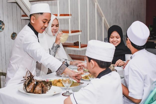 Glückliche asiatische muslimische familie, die eid mubarak mit gemeinsamem essen im speisesaal feiert