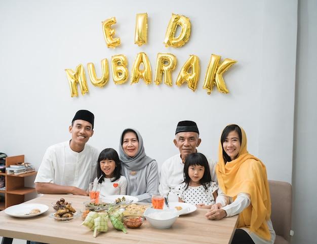 Glückliche asiatische muslimische familie feiern eid mubarak zusammen zu hause