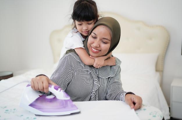 Glückliche asiatische muslimische familienmutter und kleine kleine tochter, die kleidung bügelt