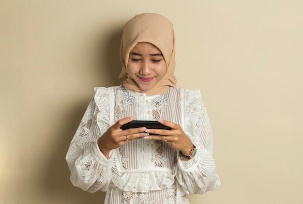 Glückliche asiatische muslimische frau aufgeregt, spiele auf ihrem smartphone zu spielen