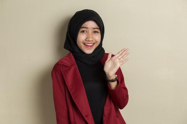 Glückliche asiatische muslimische frau sagen hallo auf grauem hintergrund