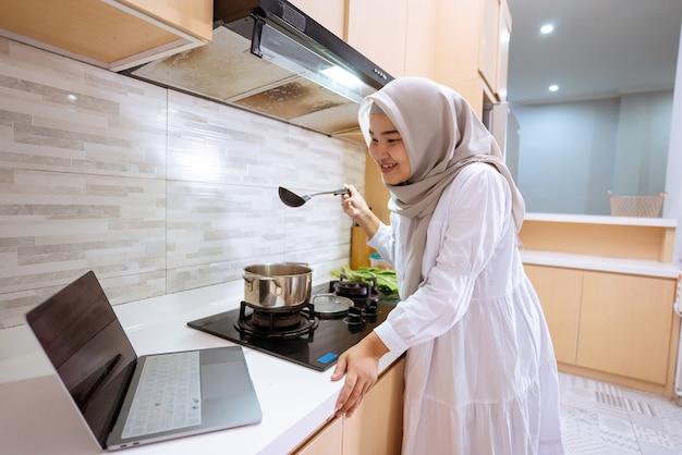Glückliche asiatische muslimische frau schauen auf ihren laptop, der lernt, wie man ein gericht zu hause kocht