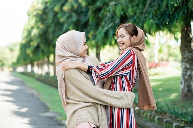 Glückliche asiatische muslimische frauen in den hijabs im freien am sonnigen tag mit freundumarmung
