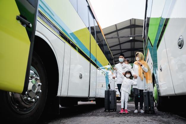 Glückliche asiatische muslimische urlaubsreise, die einen bus zusammen mit der tragenden maske der familie reitet, die die ausbreitung des virus verhindert