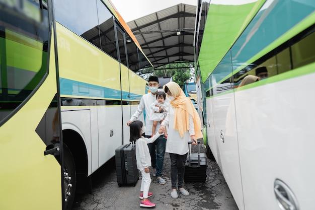Glückliche asiatische muslimische urlaubsreise, die einen bus zusammen mit der tragenden maske der familie reitet, die virusausbreitung verhindert