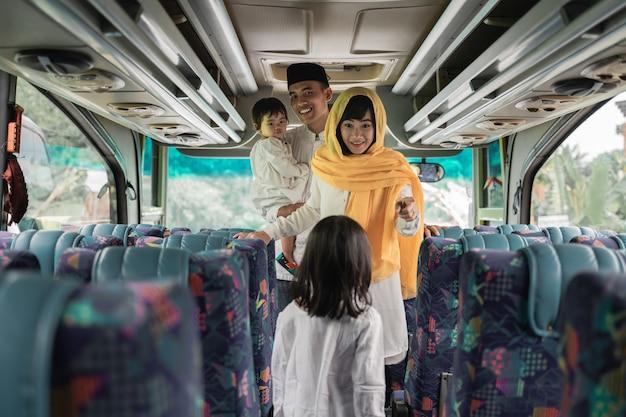 Glückliche asiatische muslimische urlaubsreise, die einen bus zusammen mit familie reitet
