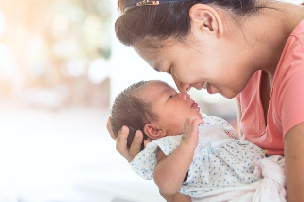 Glückliche asiatische mutter, die ihr neugeborenes baby mit liebe umarmt und küsst