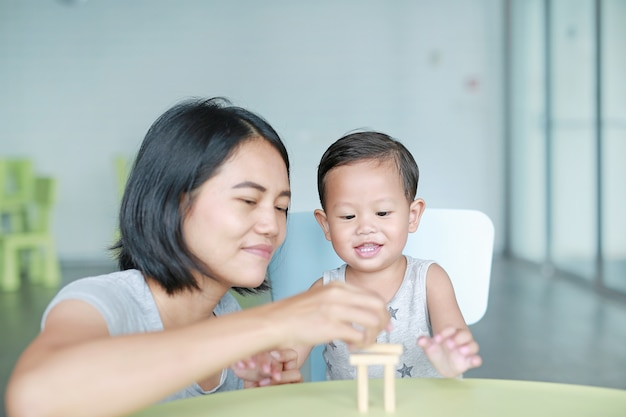 Glückliche asiatische mutter und kleines baby, die turmspiel der hölzernen blöcke für fähigkeit des gehirns und der körperlichen entwicklung in einem klassenzimmer spielt. fokus auf kindergesicht. konzept des kinderlernens und der geistigen fähigkeiten.