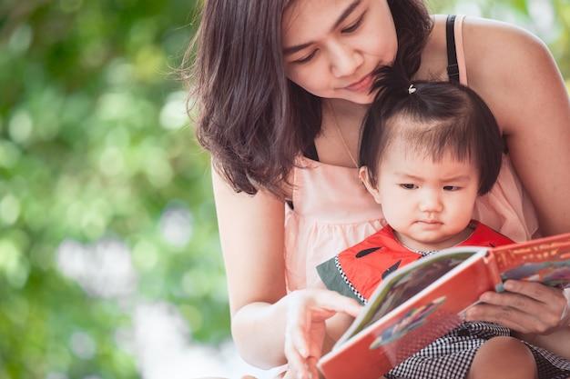 Glückliche asiatische mutter und nettes kleines baby, die zusammen ein buch mit spaß und liebe liest