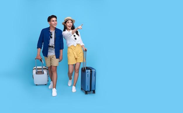Glückliche asiatische paar-touristenhand, die zeigt, raum mit gepäck zu kopieren, das an feiertagen lokalisiert auf blau reisen wird.