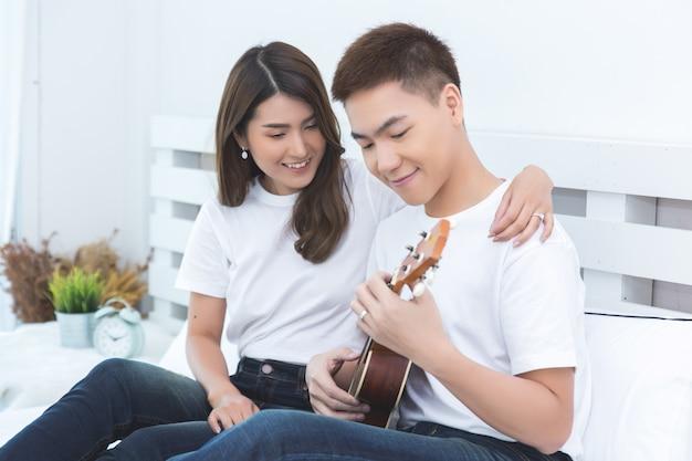 Glückliche asiatische paare auf dem bett zu hause
