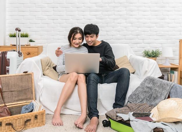Glückliche asiatische paare, die das hotel für reise mit technologielaptop planen und buchen
