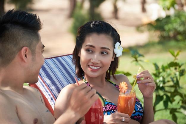 Glückliche asiatische paare, die draußen in den sonnenruhesesseln am erholungsort sitzen und frischen saft trinken