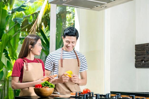 Glückliche asiatische paare, die gemüsebestandteile für das kochen zubereiten