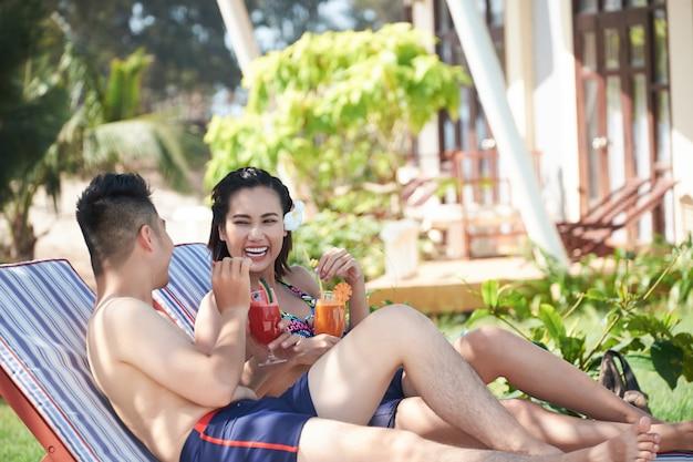 Glückliche asiatische paare, die in den ruhesesseln mit cocktails am luxuriösen erholungsort stützen