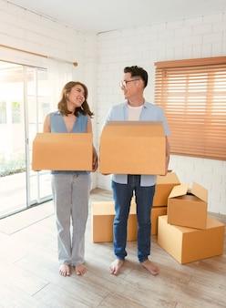 Glückliche asiatische paare, die pappkarton halten, gehen in neues zuhause. umzugskonzept