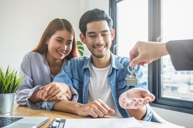 Glückliche asiatische paare, die wohnungsschlüssel vom immobilienmakler / -makler empfangen.