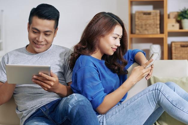 Glückliche asiatische paare, die zu hause auf couch mit geräten sitzen