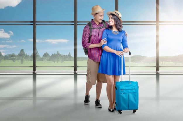 Glückliche asiatische paare, die zum reisen mit flugzeug gehen