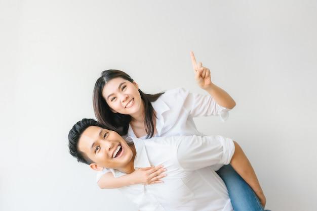 Glückliche asiatische paare in der liebe, die spaßdoppelpolfahrt hat