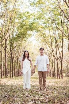 Glückliche asiatische paare in der liebe mit baumbogen