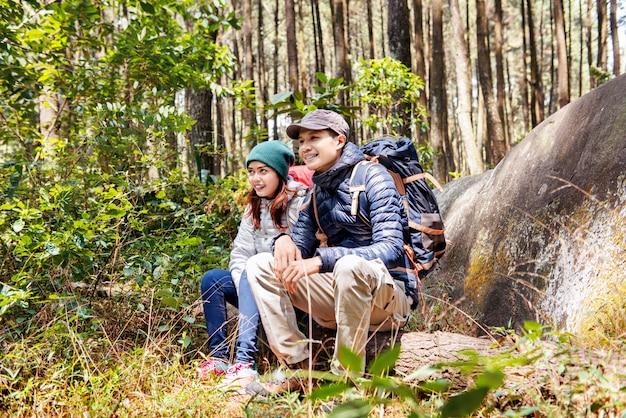 Glückliche asiatische paarwanderer sitzen auf einem baumstamm beim stillstehen
