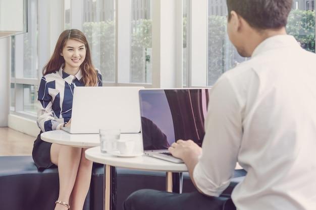 Glückliche asiatische schöne junge geschäftsfrau, die den laptop und die unterhaltung verwendet