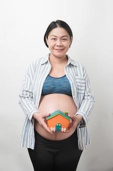 Glückliche asiatische schwangere mutter im lächeln gesicht halten und zeigen das hausförmige sparschwein, isoliert, schwangerschaftskonzept