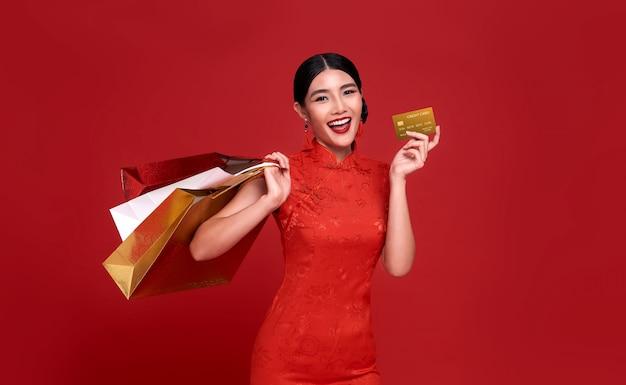 Glückliche asiatische shopaholic frau, die traditionelles cheongsam qipao kleid hält, das kreditkarte und einkaufstasche lokalisiert auf rotem hintergrund hält. frohes chinesisches neujahr
